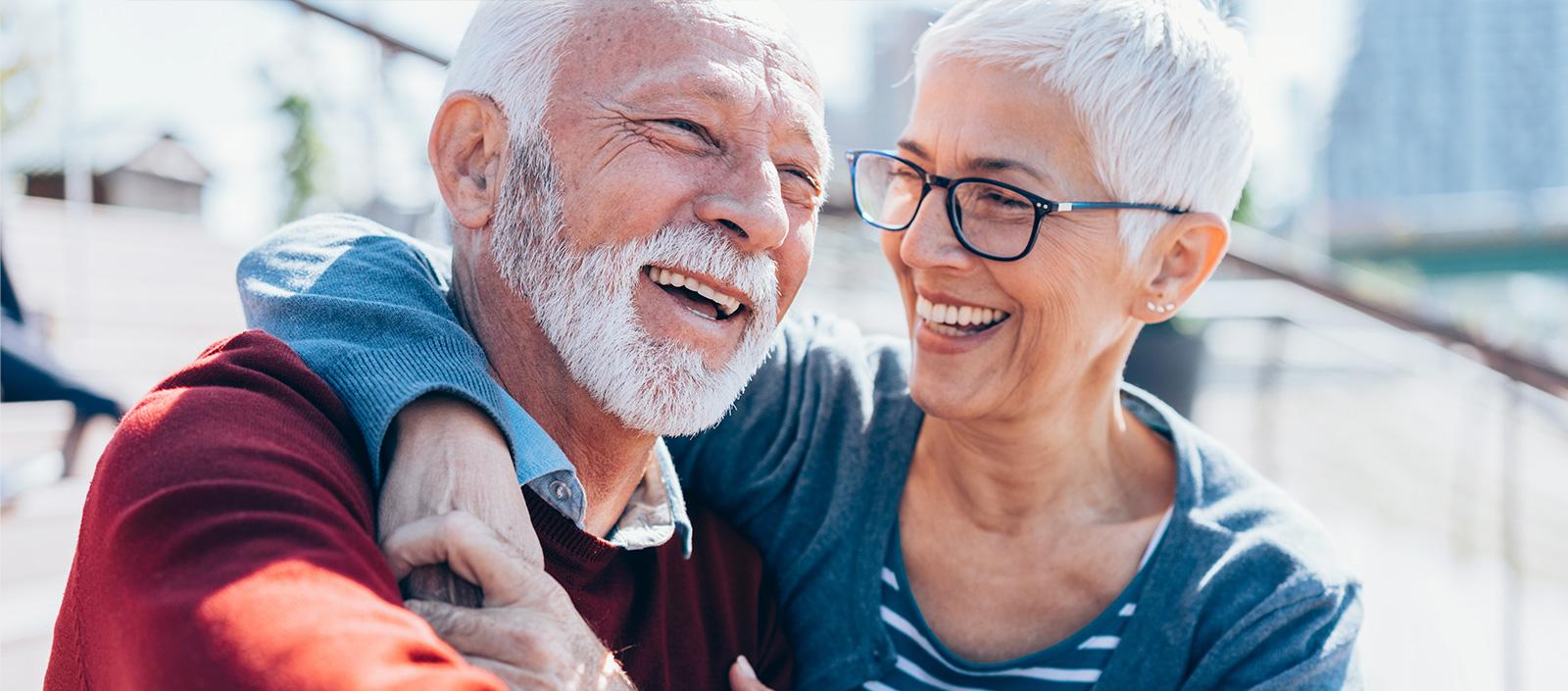 Ein älteres Ehepaar lacht nach einer erfolgreichen Zahnimplantat Behandlung